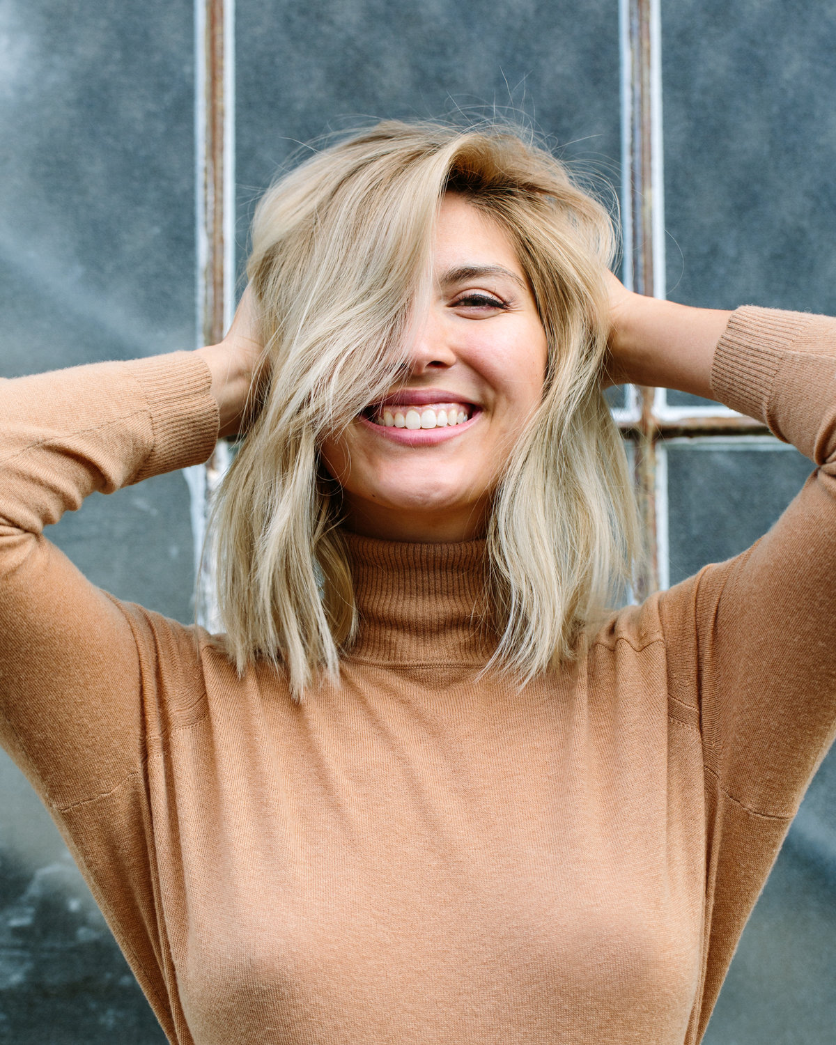blonde woman in brown turtle neck smiling at camera