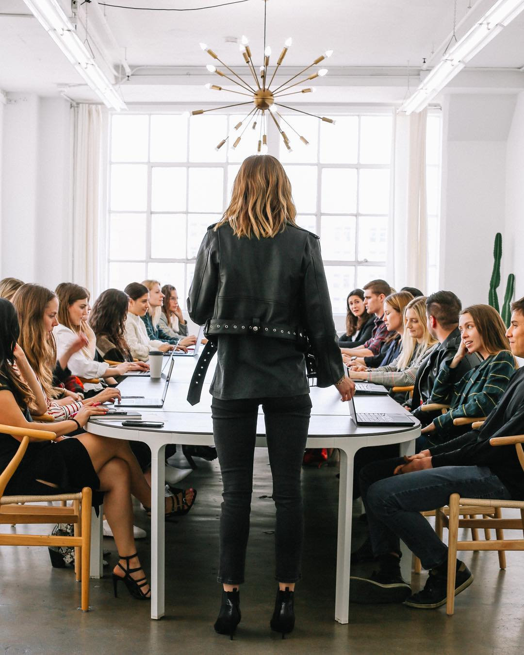woman in leather jacket leading conference in white room