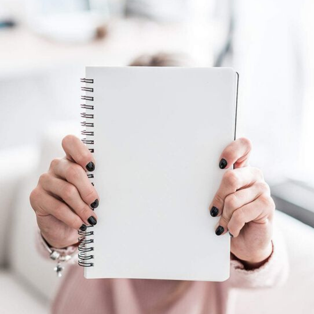 woman holding blank spiral notebook