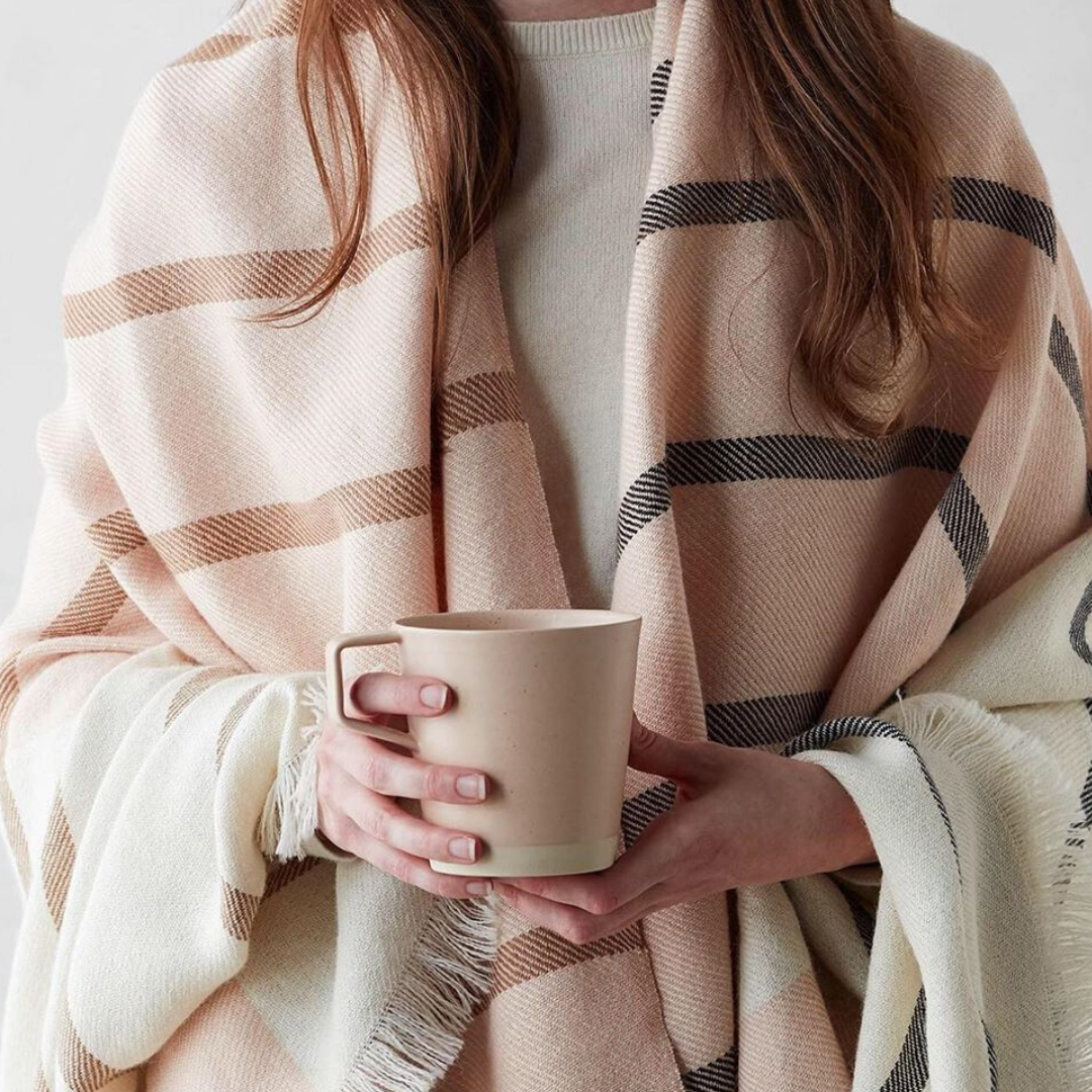 woman wrapped in a blanket holding a cup of tea