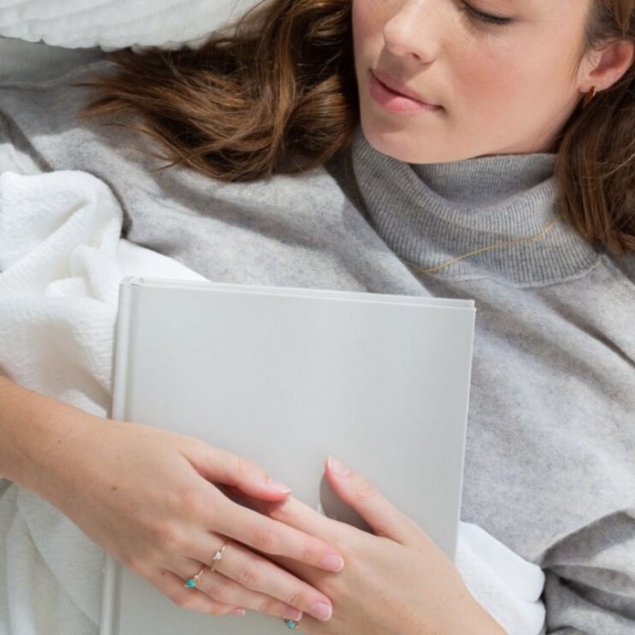 sleeping woman in grey sweater holding journal
